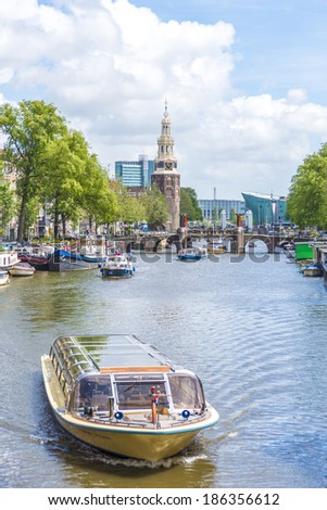 AMSTERDAM, NETHERLANDS �¢?? JUNE 16, 2013: The Montelbaanstoren tower on Oudeschans canal in Amsterdam, Netherlands, built in 1516 for the purpose of defending the city. - stock photo
