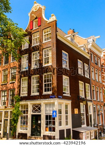 AMSTERDAM, NETHERLANDS - JUNE 1, 2015: Typical colorful houses on the Canal of Amsterdam. Amsterdam is the capital city and most populous city of the Kingdom of the Netherlands