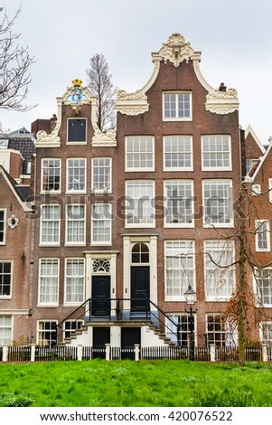 Amsterdam, Netherlands - March 31, 2016: Begijnhof courtyard with historic Holland houses in Amsterdam, Netherlands - stock photo