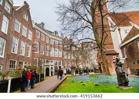 Amsterdam, Netherlands - March 31, 2016: Begijnhof courtyard with nun statue, historic houses and tourists in Amsterdam, Netherlands - stock photo