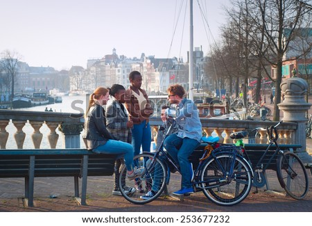 AMSTERDAM, NETHERLANDS - MARCH 10, 2104: Multicultural friends in conversation on Amsterdam street. About 177 different nationalities are residing in Amsterdam, most multicultural city in the world. - stock photo