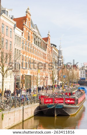 AMSTERDAM, NETHERLANDS - MARCH 7, 2015: Tourists walking by a canal in Amsterdam. Amsterdam is the capital of the Netherlands and the canals and harbours fill a full quarter of the city surface. - stock photo