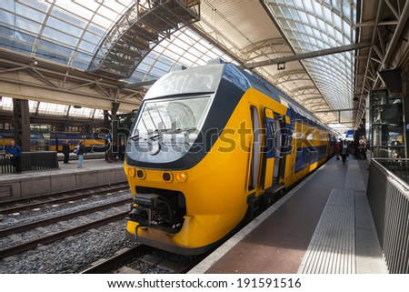 AMSTERDAM, NETHERLANDS - MARCH 19, 2014: Yellow train stands on the central railroad station in Amsterdam - stock photo