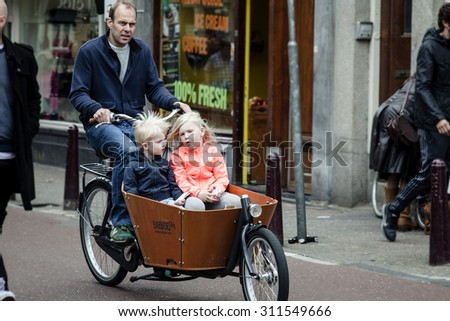 AMSTERDAM, NETHERLANDS - MAY 9: Father with two children  riding bicycles in historical part in Amsterdam, Netherlands on May 9, 2015 - stock photo