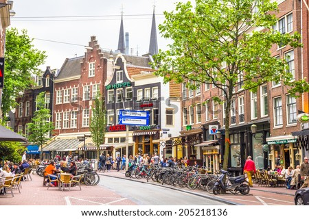 AMSTERDAM, NETHERLANDS - MAY 31, 2014: People drinking on the streets of Amsterdam. Most cafes have terraces in summertime and are full of people enjoying the weather and drinks. - stock photo