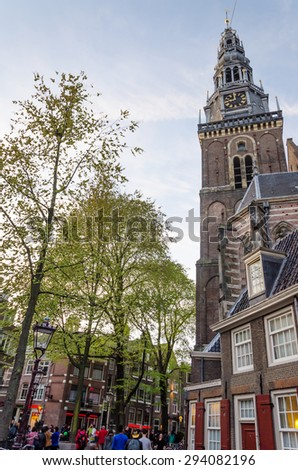 Amsterdam, Netherlands - May 8, 2015: Tourists around Old Church (Oude Kerk) - the oldest building and oldest parish church, founded in 1213, Amsterdam. It stands in main red-light district.  - stock photo