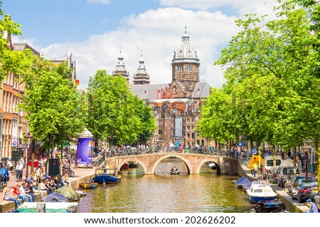 AMSTERDAM, NETHERLANDS - MAY 31, 2014: Tourists walking by a canal in Amsterdam. Amsterdam is the capital of the Netherlands and the canals and harbours fill a full quarter of the city surface. - stock photo
