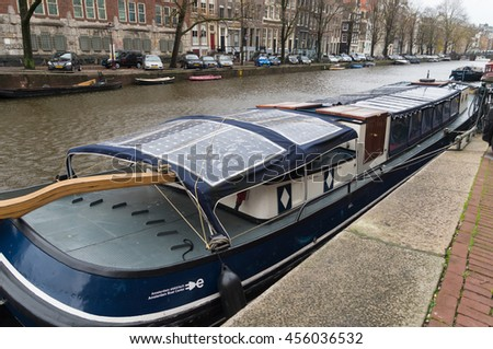 AMSTERDAM, NETHERLANDS - NOVEMBER 15, 2015: Bark with solar panels on the roof in an amsterdam canal