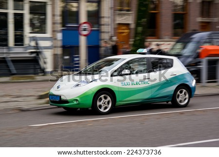 AMSTERDAM, NETHERLANDS - NOVEMBER 8: Electrical taxi car Nissan Leaf in capital citty of Netherlands, Amsterdam, on November 8, 2013. The fleet of these electrical taxis is driven in Amsterdam. - stock photo