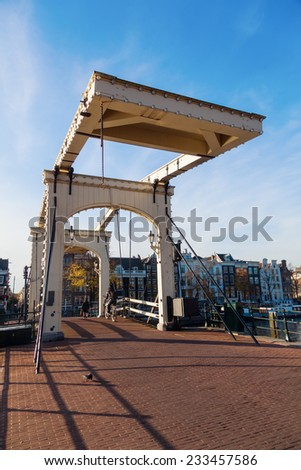AMSTERDAM, NETHERLANDS - NOVEMBER 13: old drawbridge with unidentified people on November 13, 2014 in Amsterdam. It is the capital of Netherlands with more than 3.66 mio international visitors a year