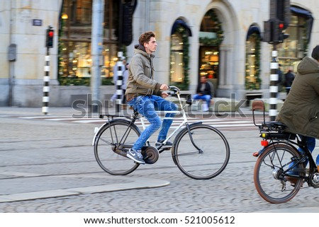 Amsterdam,Netherlands - November 22, 2016 : Panning shot of a man on bicycle with red traffic light on the road in the center of Amsterdam during winter time