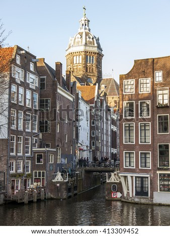 AMSTERDAM, NETHERLANDS on MARCH 28, 2016. Typical urban view in the spring evening. The bridge through the canal and buildings of the XVII-XVIII construction on embankments