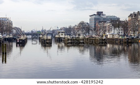 AMSTERDAM, NETHERLANDS on MARCH 31, 2016. Typical urban view in the spring. The river Amstel and buildings of the XVII-XVIII construction on embankments. Houseboats near bank