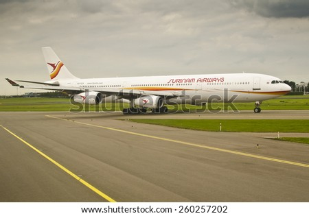 AMSTERDAM, NETHERLANDS - SEPTEMBER 27: Surinam Airways Airbus A340 at Schiphol Airport on September 27, 2014 in Amsterdam, Netherlands. Surinam Airways is the flag carrier airline of Suriname. - stock photo