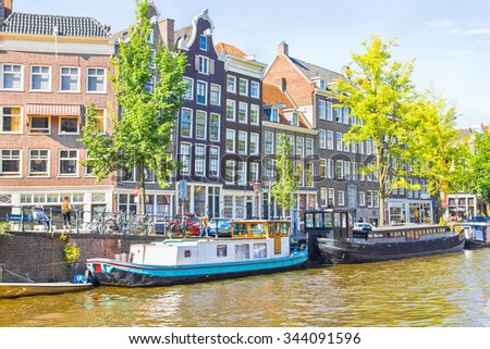 AMSTERDAM, NETHERLANDS - SEPTEMBER 3, 2012: Tourists walking by a canal in Amsterdam. Amsterdam is the capital of the Netherlands and the canals and harbours fill a full quarter of the city surface. - stock photo