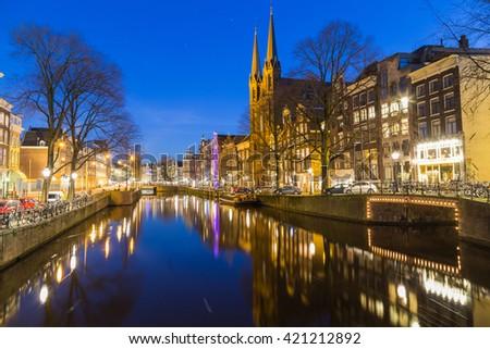AMSTERDAM, NETHERLANDS - 16TH FEBRUARY 2016: A view along the Keizersgracht canal in Amsterdam at night. Reflections, buildings, bikes and cars can be seen.