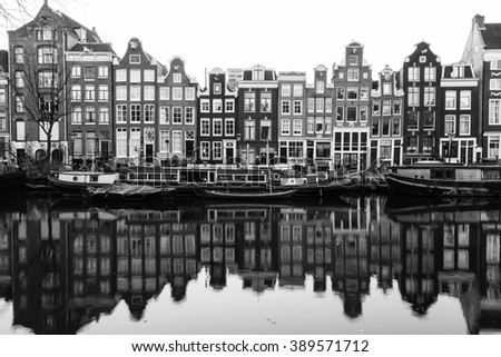 AMSTERDAM, NETHERLANDS - 16TH FEBRUARY 2016: A view of buildings and boats along the Amsterdam Canals. Reflections can be seen in the water. - stock photo