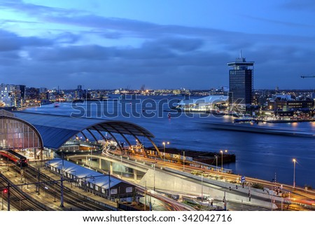 AMSTERDAM - NOVEMBER 13: Twilight scene of Amsterdam's Ij River with the new landmarks A'dam Toren and The Eye across the water from the Central Station on the evening of November 13th, 2015. - stock photo