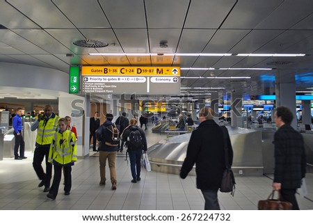 AMSTERDAM/SCHIPHOL, THE NETHERLANDS, 26 MARCH 2015 - Airplane passengers hurrying to the security check on Amsterdam Airport Schiphol. - stock photo