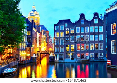 Amsterdam: St. Nicolas Church and Canals at dusk.  - stock photo