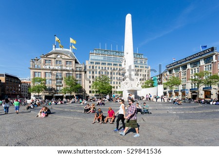 AMSTERDAM, THE NETHERLANDS - AUG 06, 2015: People near the Dutch National War Memorial at central plaza De Dam in Amsterdam