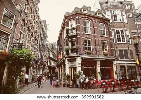 AMSTERDAM, THE NETHERLANDS - AUGUST 16, 2015: People walk on the street Gravenstraat, Street life, bars and restaurants in Amsterdam. Amsterdam is capital of the Netherlands on August 16, 2015. - stock photo