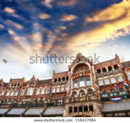 Amsterdam, The Netherlands. Beautiful classic city architecture with country flags and dramatic sky. - stock photo