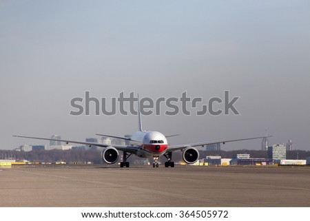 AMSTERDAM, THE NETHERLANDS - FEBRUARY 18, 2015: Parked just landed cargo boeing 777 , with on the background  the skyline of  Amsterdam on february 18 , 2015 in Amsterdam (Schiphol ), Holland.  - stock photo