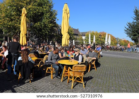 Amsterdam, The Netherlands - October 16, 2016: Young people sit at a sidewalk cafe in the sun on a canal with autumn trees in Amsterdam, The Netherlands on October 16, 2016