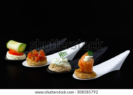 Amuse bouche: mini tartines (with smoked salmon, various types of cheese, fresh dill, cucumber, tomatoes and toast bread) on black and white designer spoons and black background. - stock photo