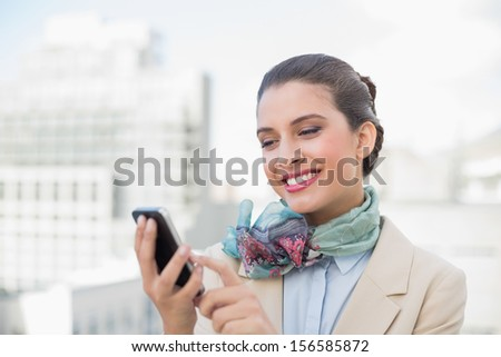 Amused smart brown haired businesswoman using a mobile phone outdoors - stock photo