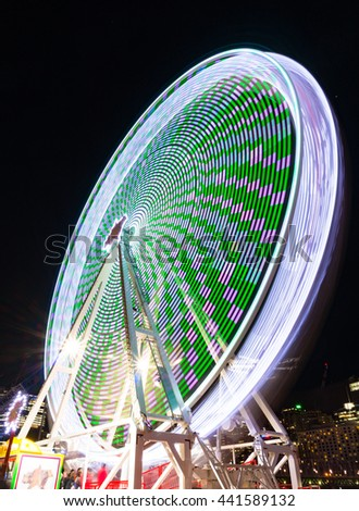 Amusement park attractions. Spinning ferris wheel at night. Motion blur - stock photo