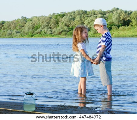 amusing boy and girl on the river summer day.toned.toned - stock photo