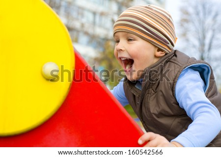Amusing boy clambering on a children's hill - stock photo