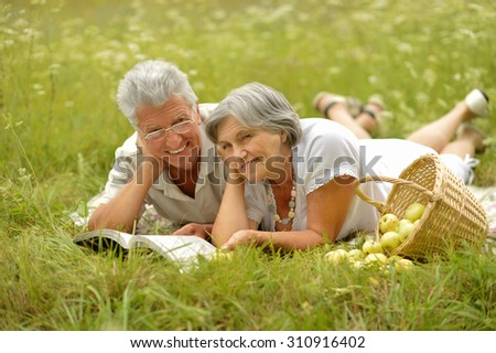 Amusing old couple on picnic with apples on grass