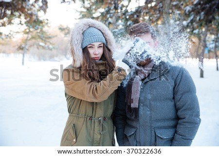 Amusing pretty young woman thowing snowball in her boyfriend face  - stock photo