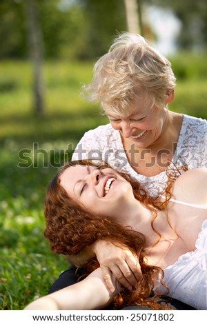 Amusing rest on the nature of mother with the adult daughter - stock photo