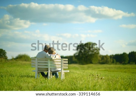 Amusing senior couple sitting on bench in park