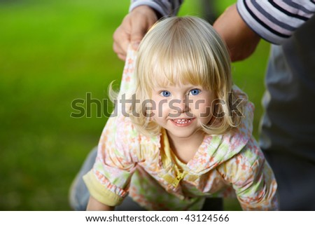 Amusing small blonde girl with blue eyes - stock photo