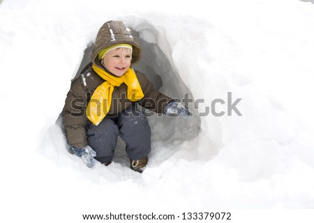 Amusing smiling kid in the winter in a snow cave - stock photo