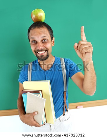 Amusing teacher literature with an apple on her head. Photo adult teacher near blackboard, education concept - stock photo
