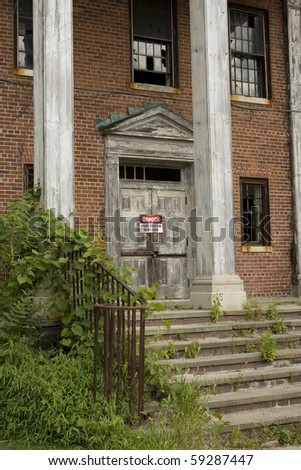 """An abandoned Building with a """"Danger Unsafe"""" sign on it. - stock photo"""