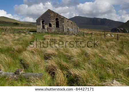 An abandoned, crumbling, chapel with no windows and doors lays rotting on an hillside with grasses and a mountain in the background.