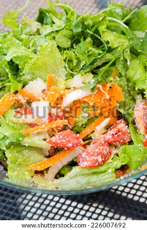 An above angle of a glass bowl full of salad with parmesan cheese - stock photo