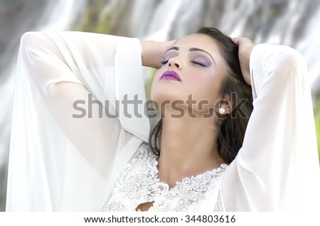 An absolutely gorgeous young woman standing in front of a rushing waterfall. - stock photo