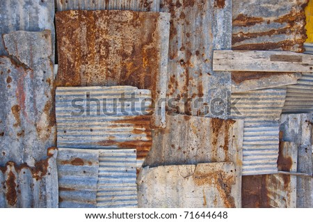 An abstract background image of rusty corrugated iron sheets overlapping to form a wall or fence. - stock photo