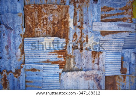 An abstract background image of the flag of Micronesia painted on to rusty corrugated iron sheets overlapping to form a wall or fence. - stock photo