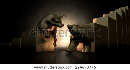 An abstract closeup of two gold cast statuettes depicting a stylized bull and a bear in dramatic contrasting light representing a financial market trends on an isolated dark background - stock photo