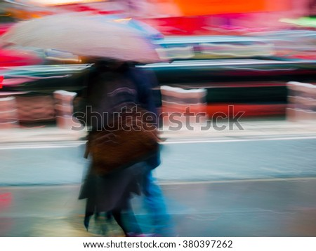 An abstract colorful motion blur of a couple with an umbrella in the streets of New York City. - stock photo