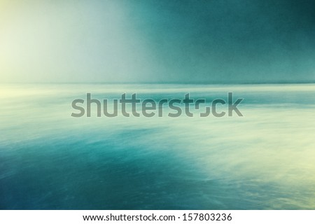 An abstract ocean seascape with blurred panning motion.  Image displays a retro, vintage look with cross-processed colors and a pleasing paper grain and texture. - stock photo